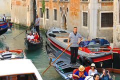 Several gondolas with tourists in a narrow channel. Venice, Ital Royalty Free Stock Photography