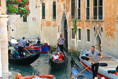 Several gondolas with tourists in a narrow channel. Venice, Ital Stock Photography