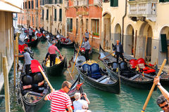 Several gondolas with tourists in a narrow channel. Venice, Ital Royalty Free Stock Images