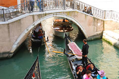 Several gondolas with tourists in a narrow channel. Venice Royalty Free Stock Images