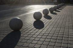 Several granite balls on a sidewalk Stock Photography