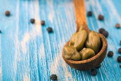 Several green capers on blue wooden table with spilled spice_ Stock Photos