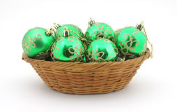 Several green Christmas ornaments in basket Stock Images