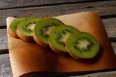 Several green kiwi slices on brown paper sheet Stock Images