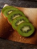 Several green kiwi slices on wet paper sheet Royalty Free Stock Photos