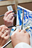 Several hands with brushes paint picture paints Stock Photography