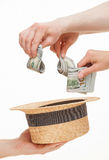 Several hands put dollars in a straw hat Stock Photos