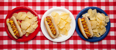 Several hotdogs on colored plates Royalty Free Stock Image