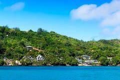 Several hotels on green shore of La Digue island, Seychelles. Stock Photos