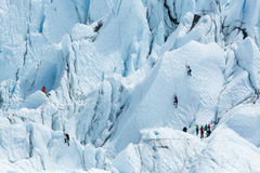 Several ice climbers looking for different route up. Several climber try to reach one ice peak while others look from below. Two other climbers try other route Stock Photo