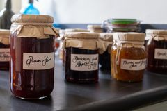 Several jars of home made jams sitting on a work top, with old fashioned brown paper and string lids with hand written royalty free stock photography