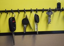 SEVERAL KEYS ON HOOKS IN A ROW. Some keys hang on a rack of hooks in an office royalty free stock photo
