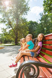 Several kids sitting on the bench in summer park Royalty Free Stock Photo