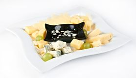 Several kinds of cheese with grapes and sauce. Plate of several kinds of cheese with grapes and sauce isolated on white by clipping path Stock Photo