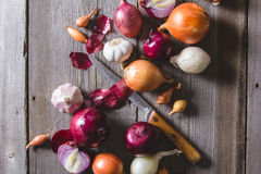 Several kinds of different onion bulbs lying on an old wooden table. Stock Photos