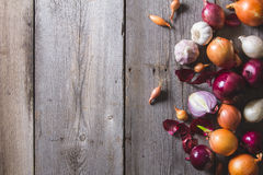 Several kinds of different onion bulbs lying on an old wooden table. Stock Images