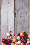Several kinds of different onion bulbs lying on an old wooden table. Stock Photography