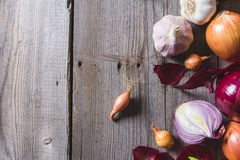 Several kinds of different onion bulbs lying on an old wooden table. Royalty Free Stock Photo