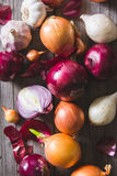 Several kinds of different onion bulbs lying on an old wooden table. Stock Image