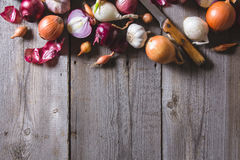 Several kinds of different onion bulbs lying on an old wooden table. Royalty Free Stock Photography