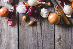 Several kinds of different onion bulbs lying on an old wooden table. Royalty Free Stock Images