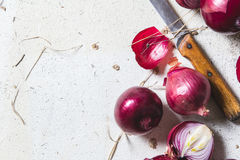 Several kinds of different onion bulbs lying on an old wooden table painted in white. Royalty Free Stock Photo