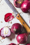 Several kinds of different onion bulbs lying on an old wooden table painted in white. Stock Photography