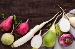 Several kinds of radish daikon, Chinese red, green on a wooden table. Useful vitamins ingredient for salads. The top view Stock Photography