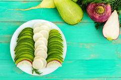 Several kinds of radish sliced on a white plate on a light wooden background Royalty Free Stock Photo