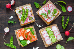 Several kinds of sandwiches with vegetables: radish, tomatoes, cucumber, arugula on crispy toast Stock Images
