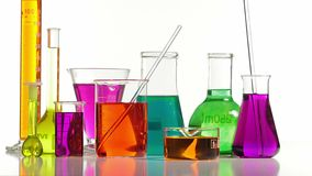 Several laboratory bottles of different shapes and colors. Effervescence within some colored containers stock video footage