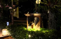 Several lanterns illuminate the bushes, on which small white flowers bloom. An elephant head sculpture adorns the small garden. Design royalty free stock photo