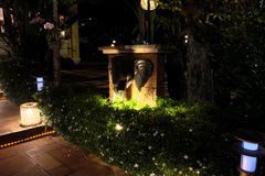 Several lanterns illuminate the bushes, on which small white flowers bloom. An elephant head sculpture adorns the small garden. Design stock image