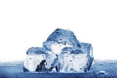 Several large ice cubes with droplets on wet table Stock Images