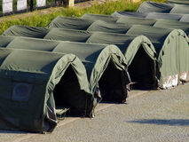 Several large military tents on the paved area Stock Images