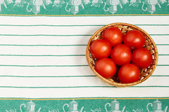 Several large red pepper lie in the wattled plate standing on a towel Stock Photo
