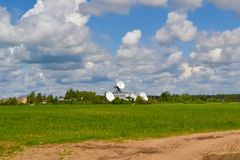 Several large satellite communication antennas in a field against a blue sky. Space Communication Center.  Stock Photo