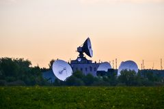 Several Large Satellite Communications Antennas In The Field In The Early Morning. Space Communication Center Royalty Free Stock Images