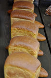 Several loaves of bread. Bread lined in a row on a wooden table royalty free stock photos