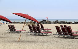 Several lounge chairs and umbrellas set at the beach Stock Photography