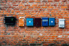 Mailboxes of different colors on a brick wall stock photo
