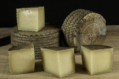 Several Manchego cheeses, one of them cutted into pieces Stock Photography