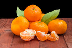 Several mandarin oranges on a dark wooden surface Stock Images