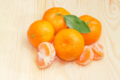 Several mandarin oranges on a light wooden surface Stock Photo