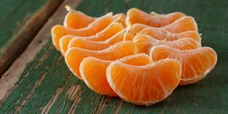 Several mandarine pieces on green board royalty free stock photos