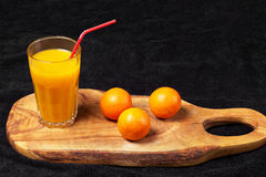 Several mature citrus and a glass of juice on a wooden table on a blackboard - mandarins.  Stock Photo