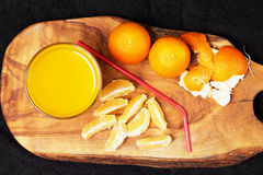Several mature citrus and a glass of juice on a wooden table on a blackboard - mandarins.  Royalty Free Stock Images