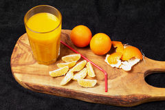 Several mature citrus and a glass of juice on a wooden table on a blackboard - mandarins.  Royalty Free Stock Photography