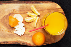 Several mature citrus and a glass of juice on a wooden table on a blackboard - mandarins.  Royalty Free Stock Photo