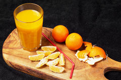 Several mature citrus and a glass of juice on a wooden table on a blackboard - mandarins.  Royalty Free Stock Photos